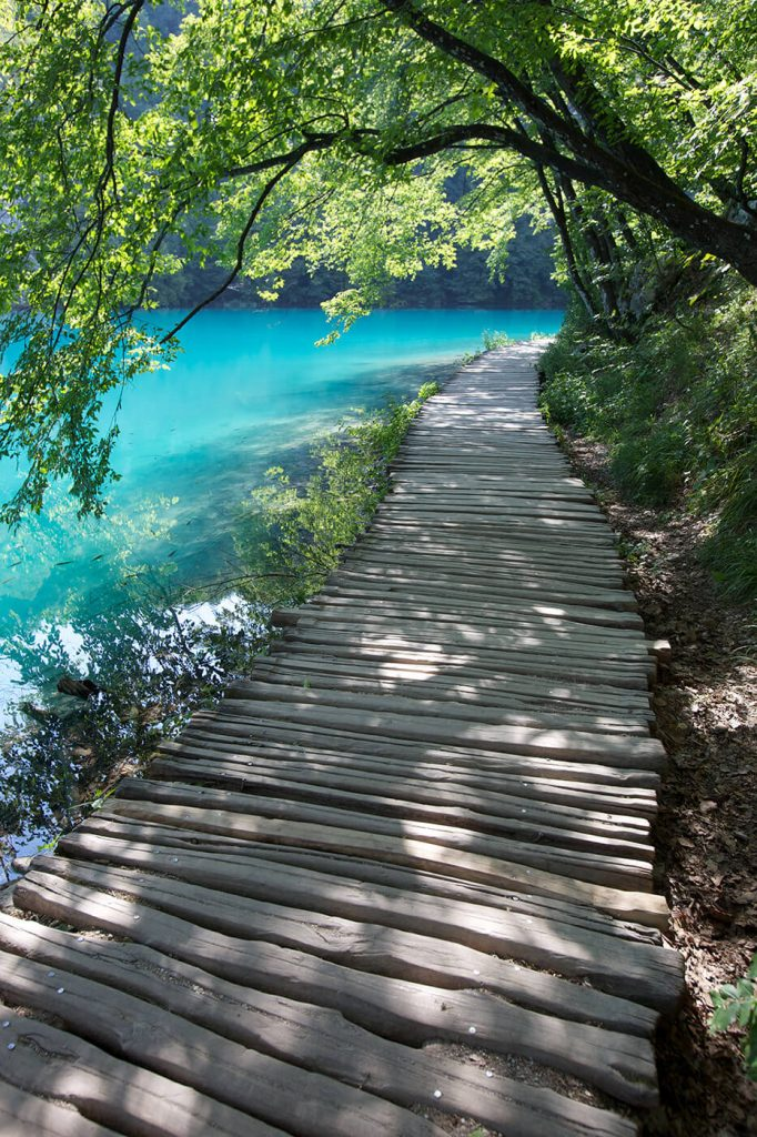 A wooden pathway trailing along the banks of a beautiful blue lake.