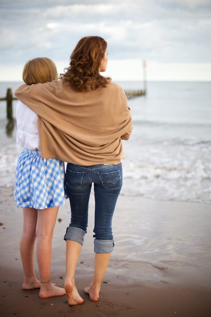 mother and teenage daughter on beach embacing