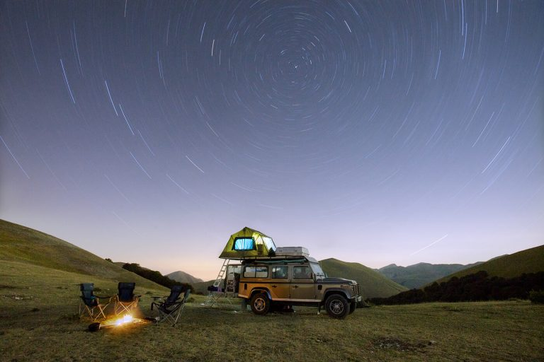 View of the night sky set behind tents and campfire in Umbria.