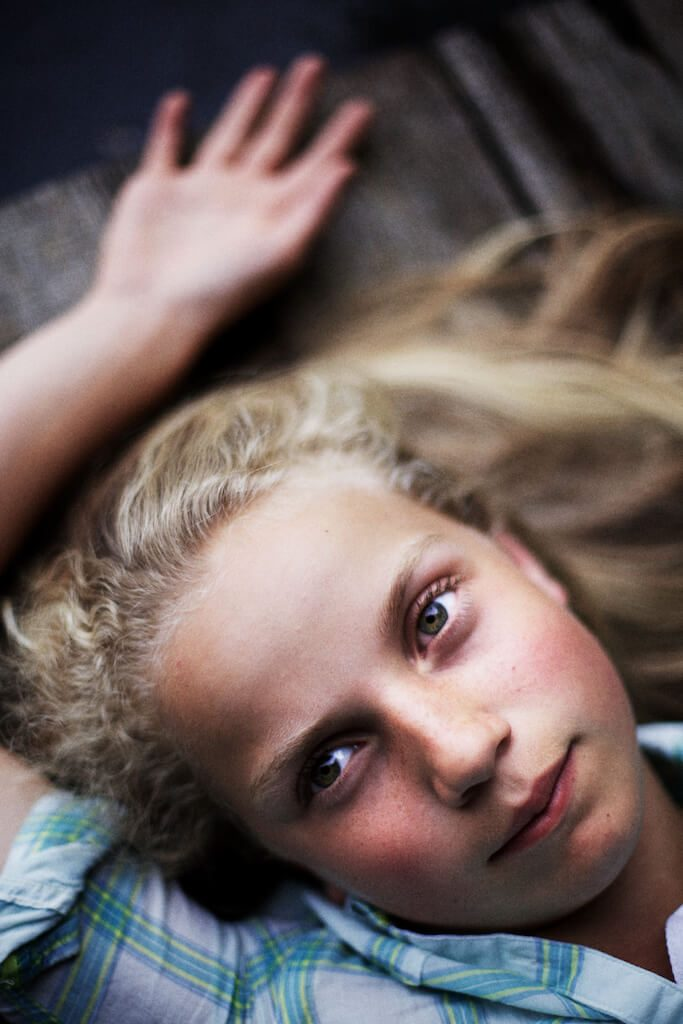 Portrait photograph of a teenage girl lying on her back.