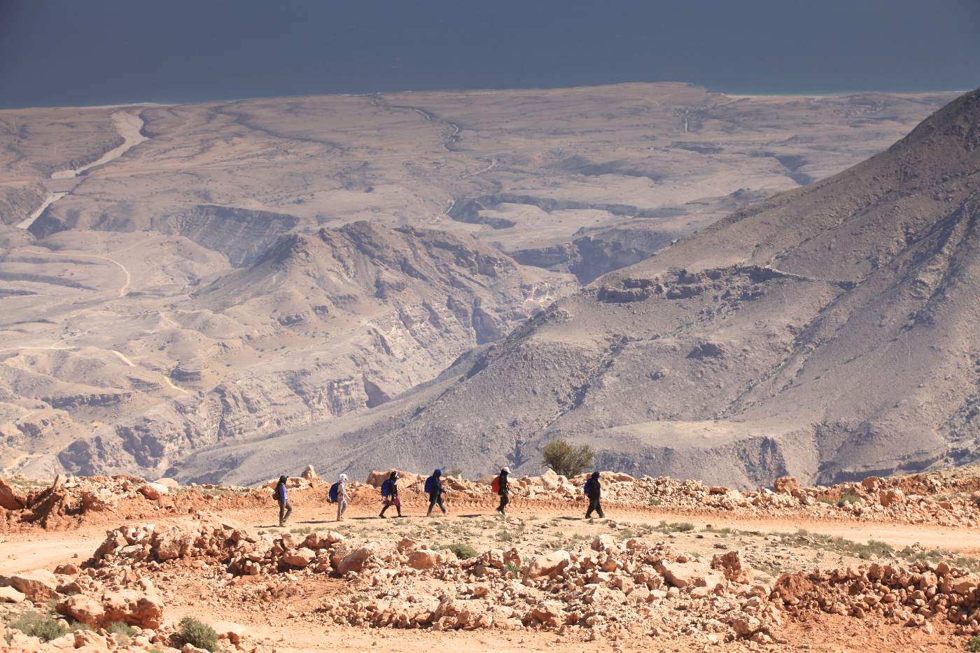 Six people trekking through the desert in Oman, with mountainous range in the background.