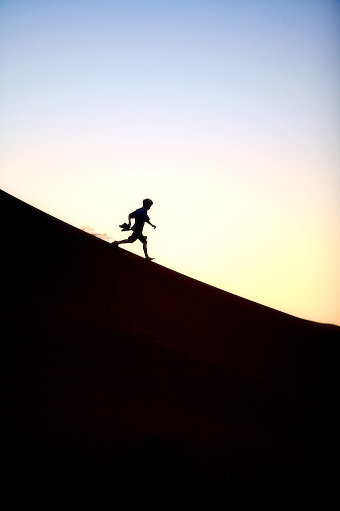 boy running down a big sand dune
