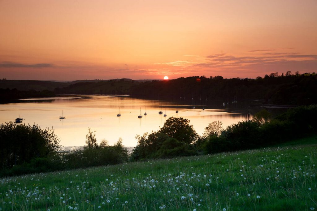 Orange sun setting over the river dart.