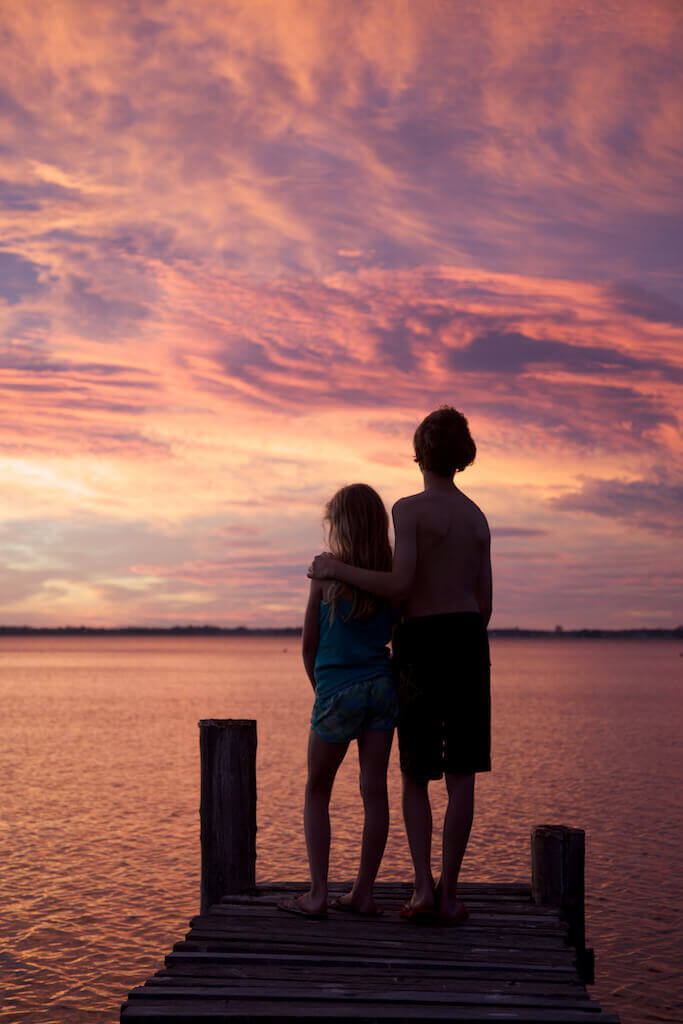The sun rises in Tasmania behind the silhouette of a boy and girl.