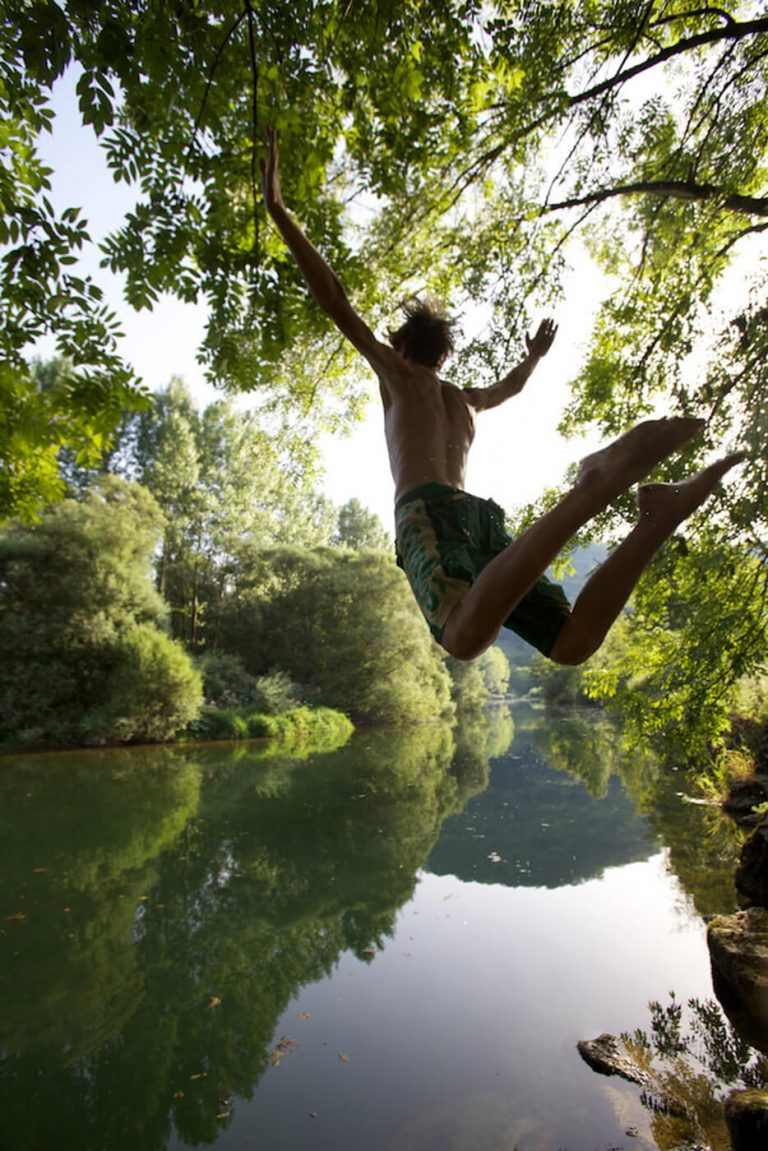 A boy leaping into a still lake in France surrounded by forest.